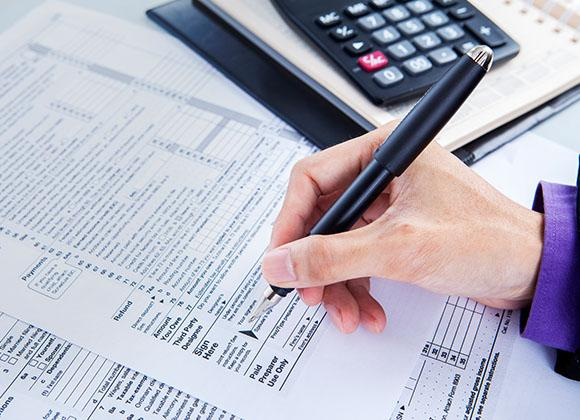 Hands Writing on Paper with Calculator for Tax Accounting and Accounting Services in Sandy Springs, GA